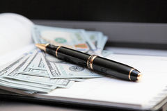 Ball pen against banknotes. Royalty Free Stock Images