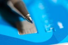 Ball pen on blue credit card . Ball pen on blue credit card close up macro shot Stock Photos