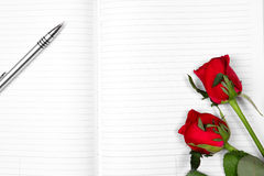 Ball pen & red rose  on Empty note book Stock Photo