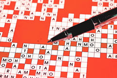 Ball point pen. On the background of crossword Royalty Free Stock Image