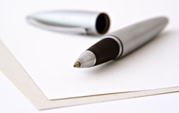 Ball-point pen on blank papers. A silver ballpoint pen and it's cap lying on two sheets of blank structured paper stock photos