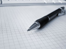 Ball-point pen on graph paper. Ball-point pen lying on graph paper, shallow depth of field, computer keyboard in background royalty free stock image