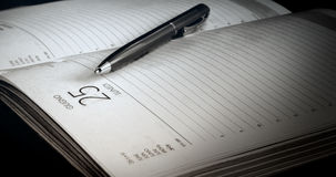 The ball-point pen lies on the open page of the daily log. Мonochrome.Blackout at the edges. Horizontal format indoors. Without people. Photo Royalty Free Stock Images