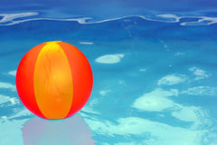 Ball in the pool. Inflatable ball floats in the water in the pool stock photography