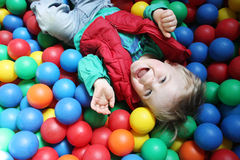 Ball pool boy. Two year old boy in a pool of coloured balls royalty free stock images