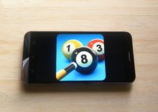 8 Ball Pool on mobile phone. 8 Ball Pool game app on smartphone kept on wooden table royalty free stock image