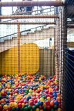 Ball pool with a net for children. games for children in the amu. Sement park, amusement area with a pool of colored soft balls, swimming in colored balls royalty free stock photos