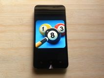8 Ball Pool on smartphone. 8 Ball Pool game app on smartphone kept on wooden table stock images