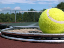 Ball and racket. Tennis ball resting on a racket on a tennis court royalty free stock photo