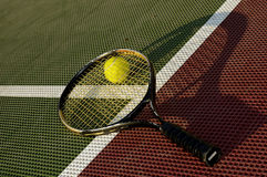 Ball and Racquet on the court. A tennis racquet and yellow tennis ball laying on the baseline of a tennis court stock photos