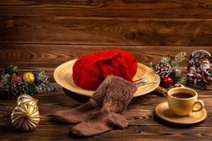 A ball of red thread in a wooden plate, brown knitted socks, a cup of tea on a saucer and Christmas decorations on wooden royalty free stock image