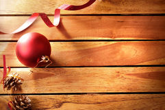 Ball ribbon and pinecone Christmas decoration on wooden table to Stock Images