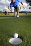 Ball rolling into the hole Stock Photos