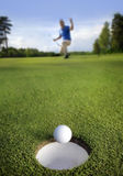 Ball rolling into the hole Stock Photography