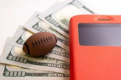 The ball for rugby or American football lies next to the phone in a red case against the background of five hundred US dollars. Bookmaker illustration. Concept royalty free stock photography