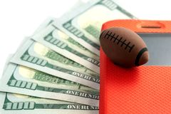 The ball for rugby or American football lies on the screen of the phone in a red case against the background of five hundred US. Dollars. Conceptual royalty free stock photography
