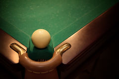 Ball for russian billiards. On green table near with hole, vignette royalty free stock images
