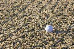Ball in the sand. Lonely golf ball in sand bunker Stock Photo