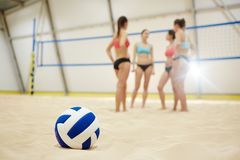 Ball on sand. Volley ball on sand field on background of four young participants having break stock photography