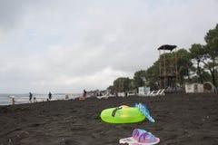Ball, schwimmende Gläser, Sandale und sich hin- und herbewegender Ring auf Strand Setzen Sie das Leben, Urlauber am Strand der Bi Stockfoto