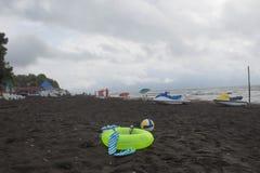 Ball, schwimmende Gläser, Sandale, Wasserfahrzeug und sich hin- und herbewegender Ring auf Strand Unscharfe Leute auf Sand setzen Stockfoto