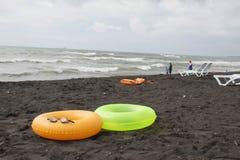 Ball, schwimmende Gläser, Touristen, sunbeds und sich hin- und herbewegender Ring zwei auf Strand Stockfotografie