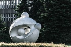 Ball sculpture. Ball white modern art sculpture with fur tree and building background Royalty Free Stock Photo