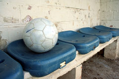 Ball on seats. A soccer ball on blue dug-out seats royalty free stock image
