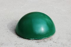 Ball-shaped concrete pedestals near the house beside the road against the entry of vehicles. Relevant when the danger of terrorist. Ball-shaped green concrete Stock Images