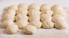 Ball-shaped pieces of dough prepared for pies making. Ball-shaped dough pieces sprinkled with flour prepared for pies making on the table Stock Photos