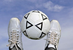 The ball in the sky. Soccer ball between the legs on the background of the sky Stock Photos