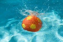 Ball splashing in pool Royalty Free Stock Photography