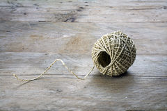 Ball of string with texture and strands on rustic gray wood Royalty Free Stock Photos