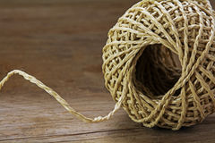 Ball of string with texture and strands on a wooden background, Stock Image