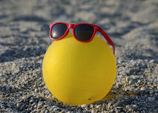 Ball in sunglasses on summer beach Stock Images