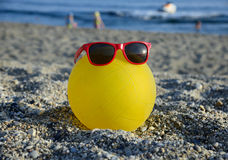 Ball in sunglasses on summer beach Royalty Free Stock Photo
