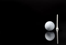 A Ball and a Tee. Image of a golf ball and a tee with reflection royalty free stock photos