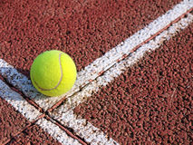 Ball on a tennis court. Yellow tennis ball on a red tennis court Royalty Free Stock Photography