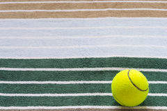 Ball for tennis on a towel. Yellow ball on a towel with stripes Stock Images