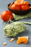 Ball of thread with knitting needle and fresh mandarins on gray background Stock Image