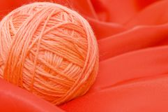 Ball of threads on a red fabric Royalty Free Stock Photography