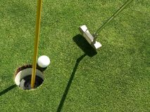 Ball about to Fall In. A putted golf ball about to drop into the cup Stock Images