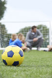 Ball Trainer-And Team Discussing Soccer Tactics With in Foregroun Lizenzfreie Stockfotos