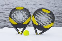 Ball and two beach tennis rackets on the snow covered beach against the background of the sea stock photo