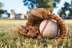 Ball und Handschuh auf dem Gebiet Stockfotos