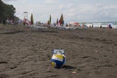 Ball und schwimmende Gläser auf Strand Unscharfes Foto von Leuten auf Sandstrand Reise oder Seeferienkonzept Stockfoto