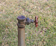 Ball valve and metal pipe in garden Royalty Free Stock Photo