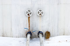 Ball valves and pipes on the tank wall. Royalty Free Stock Photos