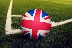 Ball Vereinigten K?nigreichs auf Ecktrittposition, Fu?ballplatzhintergrund Nationales Fu?ballthema auf gr?nem Gras stock abbildung