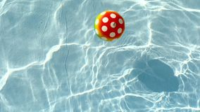 Ball in the water. Rubber ball with spots in water stock video footage